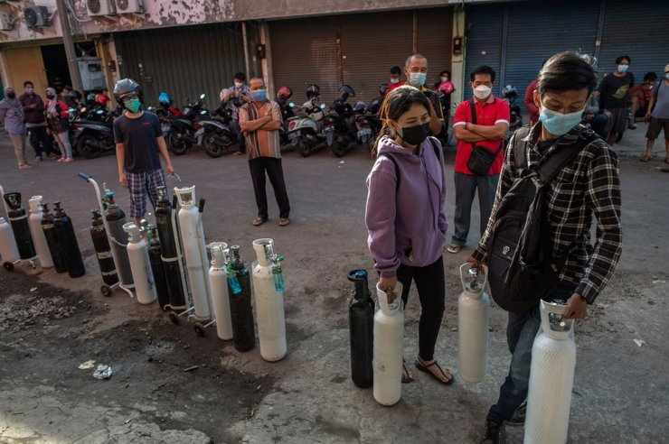 Residents queue up to get oxygen tanks refilled at a refilling station in Indonesia's second-biggest city Surabaya, July 15, after the government ordered the nation's oxygen supplies to be directed to hospitals overflowing with COVID-19 patients. Korea plans to offer $1 million worth of oxygen concentrators and other quarantine products to Indonesia, its foreign ministry said July 16. AFP-Yonhap