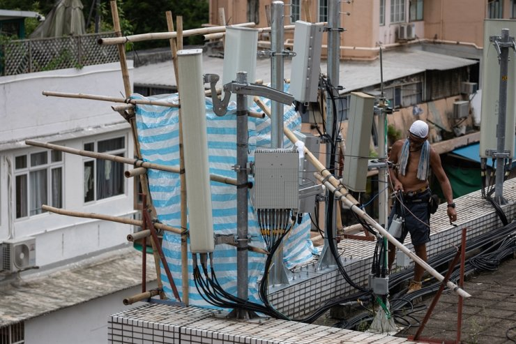 Workers install 5G antennas on a rooftop in Hong Kong in this file photo. EPA-Yonhap