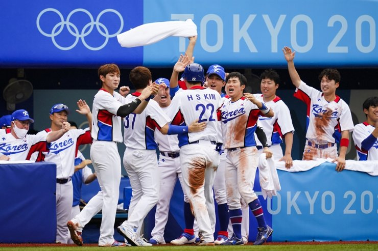 Kim Hyun-soo celebrates in the dugout after scoring on a single by Kang Baek-ho in the fifth inning of the bronze medal baseball game against the Dominican Republic at the 2020 Summer Olympics in Yokohoma, Japan, Aug. 7. AP-Yonhap