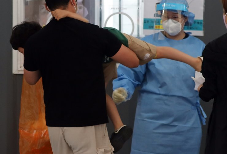 A kid refuses to get tested for COVID-19 at a testing center in Seoul Station, Aug. 31. Yonhap