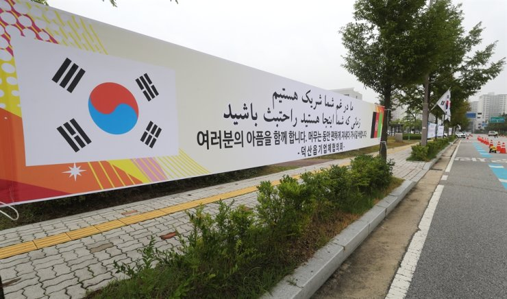 A banner in Korean and Arabic reads 'We will share your pain. Have a comfortable stay while you are here.' Banners were set up at the entrance of National Human Resources Development Institute in Jincheon. About 380 Afghan evacuees will stay there for six-weeks of education on the Korean language and their adaption to Korean culture. Yonhap
