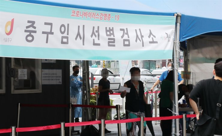 Residents wait for a COVID-19 test in a temporary center at Seoul Station, Sunday. Yonhap