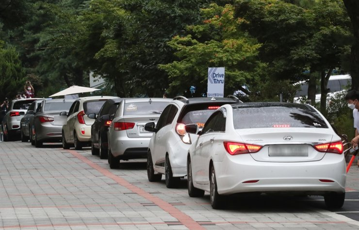 Cars are lined up at a drive-thru COVID-19 testing center in Seoul's Eunpyeong District, Monday. Yonhap