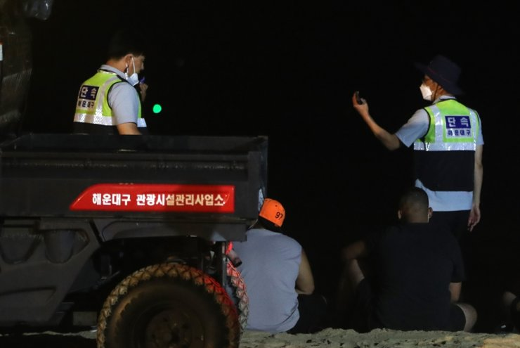 Police officers talk with vacationers who broke social distancing rules at Haeundae Beach in Busan, July 31. Yonhap