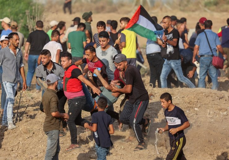 Palestinian protesters evacuate an injured youth amid clashes with Israeli security forces following a demonstration by the border fence with Israel, east of Gaza City, denouncing the Israeli siege of the Palestinian strip, Aug. 21. AFP-Yonhap