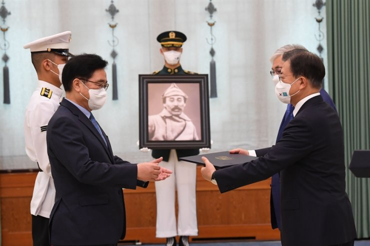 Rep. Woo Won-shik, left, chairman of the Hong Beom-do Commemoration Committee, receives the Order of Merit for National Foundation from President Moon Jae-in on behalf of Hong, a historic independence fighter, at Cheong Wa Dae, Aug. 17. Yonhap