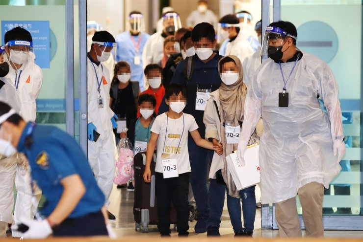 Afghan evacuees, who arrived aboard a C-130 military transport aircraft via Islamabad, leave the arrival lounge at Incheon International Airport, west of Seoul, Aug. 27. Yonhap