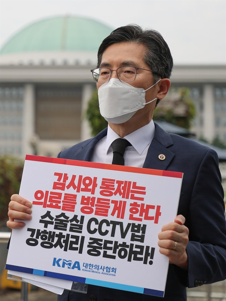 Lee Pil-soo, president of the Korean Medical Association, stages a protest in front of the National Assembly, Monday, against the Assembly's move to pass a bill that requires the installation of surveillance cameras in hospital operating rooms. A group of liberal ruling Democratic Party of Korea lawmakers proposed the bill, citing the growing need to provide protection to patients against medical negligence or malpractice, while medical groups have been against it, claiming that the legislation will create distrust between doctors and patients. Yonhap