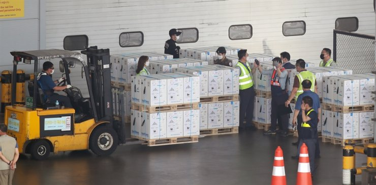 Workers move boxes of the Pfizer COVID-19 vaccine at a cargo terminal at Incheon International Airport, Wednesday. Yonhap