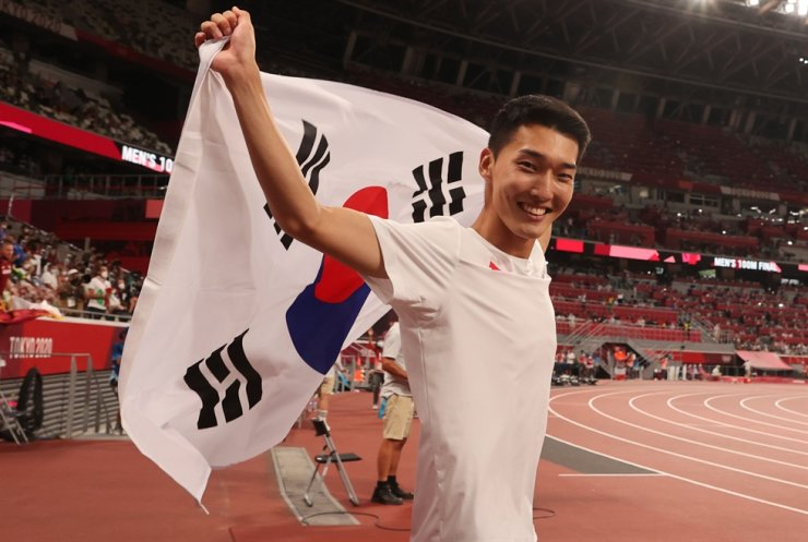 High jumper Woo Sang-hyeok poses with the Korean national flag after the finals of the men's high jump at the Olympic Stadium in Tokyo, Aug. 1. Yonhap