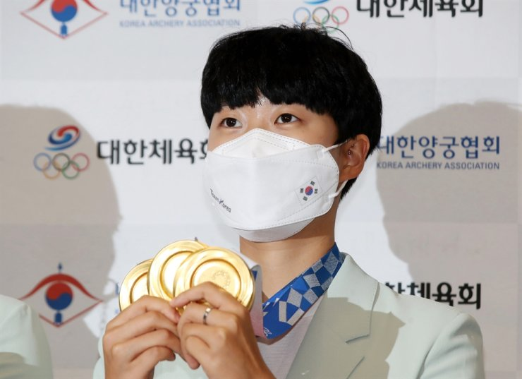 Archer An San holds up her three gold medals won at the Tokyo Olympics after arriving at Incheon International Airport, Aug. 1. Yonhap