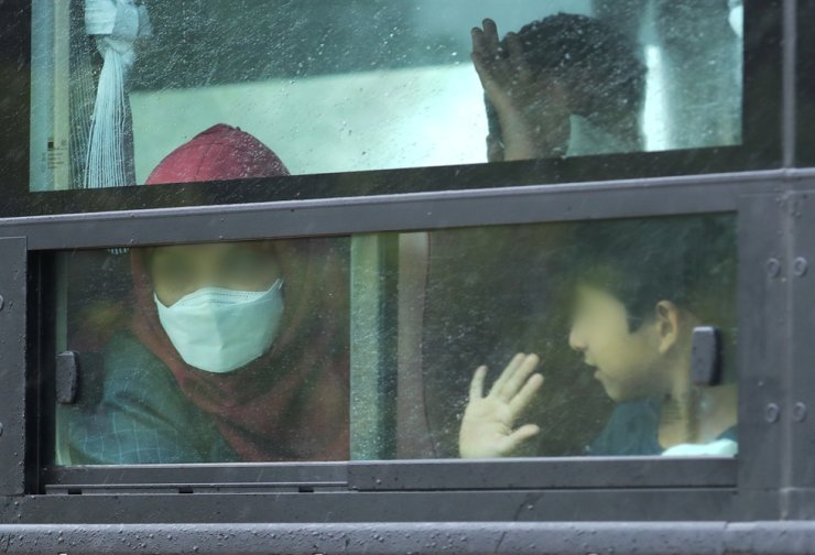 Afghans who worked for the Korean government and their families wave from a bus upon their arrival at the Leadership Campus of the National Human Resources Development Institute in Jincheon, North Chungcheong Province, Friday. They will stay at the temporary shelter for about two months. Yonhap