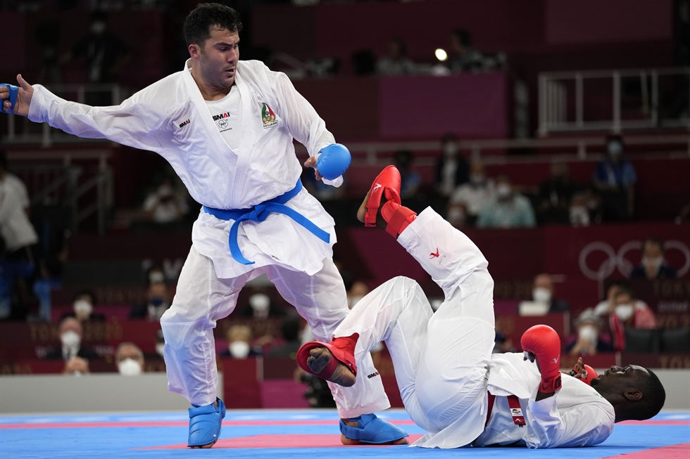 Medical personnel attend to Sajad Ganjzadeh of Iran after he was injured while competing against Tareg Hamedi of Saudi Arabia in their men's kumite +75kg gold medal bout for karate at the 2020 Summer Olympics, Aug. 7, in Tokyo. AP-Yonhap
