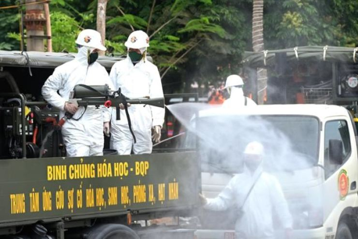 Vietnamese soldiers spray disinfectant on the streets of Hanoi, May 12. EPA-Yonhap
