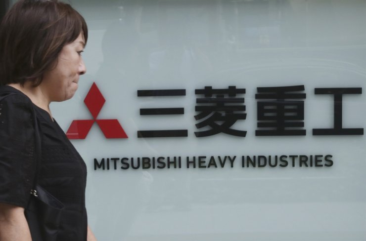 In this 2019 July file photo, a woman walks past the company sign of the Mitsubishi Heavy Industries in Tokyo. AP-Yonhap