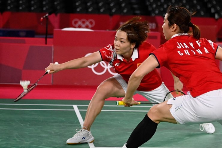 Chinese badminton player Chen Qingchen, left, hits a shot next to teammate Jia Yifan in their women's doubles badminton semi-final match against Korea's Kong Hee-yong and Kim So-yeong, at the Tokyo Olympics at Musashino Forest Plaza in Tokyo, July 31. AP-Yonhap