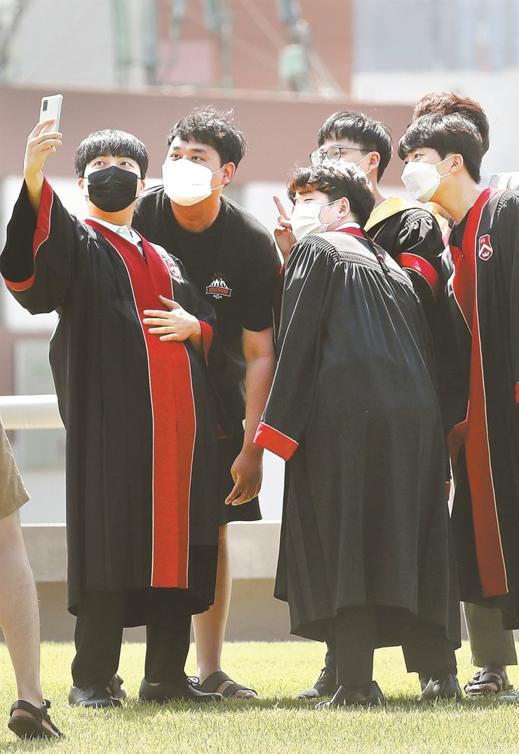 Graduates take a selfie at Sogang University during their commencement in Seoul, Tuesday. Due to the prolonged COVID-19 pandemic, a large number of universities have canceled their graduation ceremonies. Yonhap