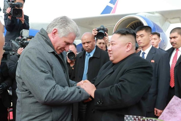 In this 2018 November file photo released by North Korea's Rodong Sinmun, North Korean leader Kim Jong-un and Cuban President Miguel Diaz-Canel hold hands at Pyongyang International Airport. Yonhap