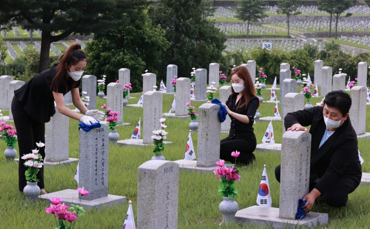 In this June 24 file photo, North Korean defectors and college students clean gravestones at the Seoul National Cemetery as volunteering work. Yonhap