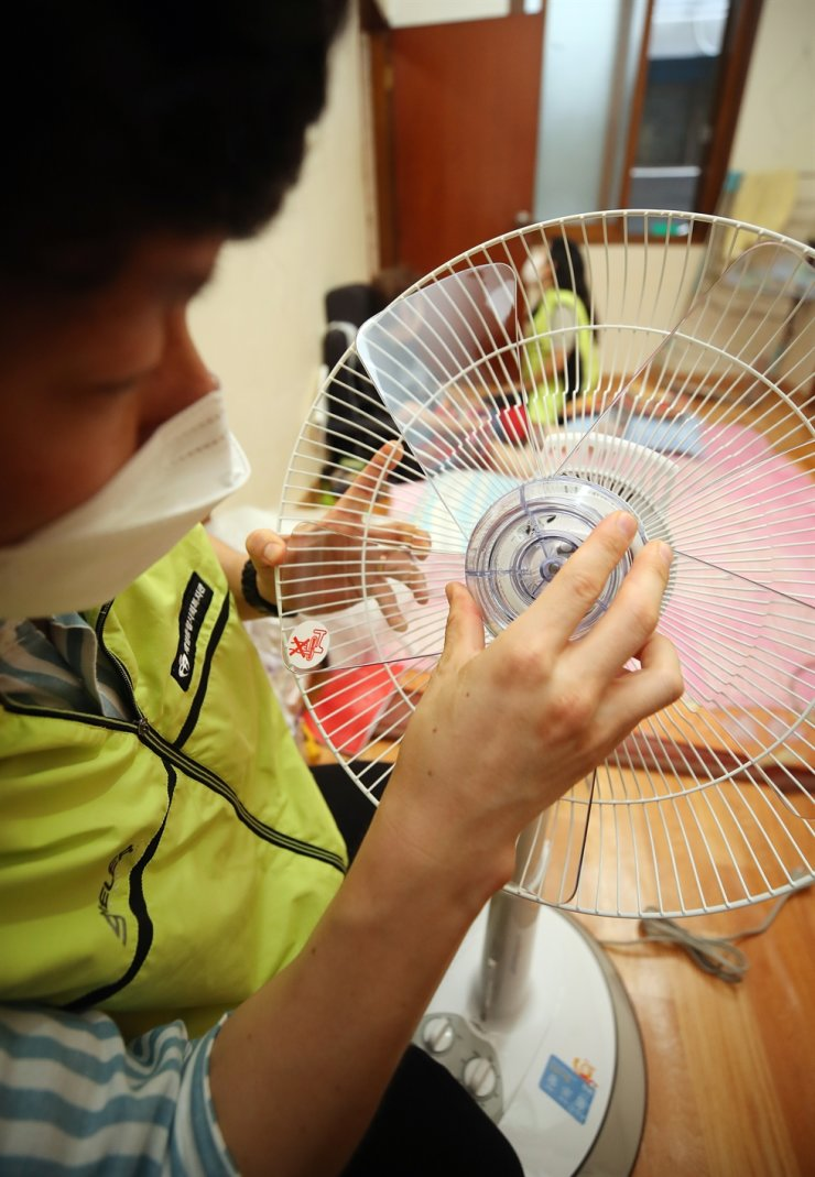 A social worker from the Jeil Community Welfare Center in Daegu's Seo District assembles a new electric fan to replace an old, out-of-order one, during visits to senior citizens living alone, Monday, as part of a welfare policy to help the underprivileged elderly fight the heat wave. The center also provides shelters where citizens can cool off. Yonhap