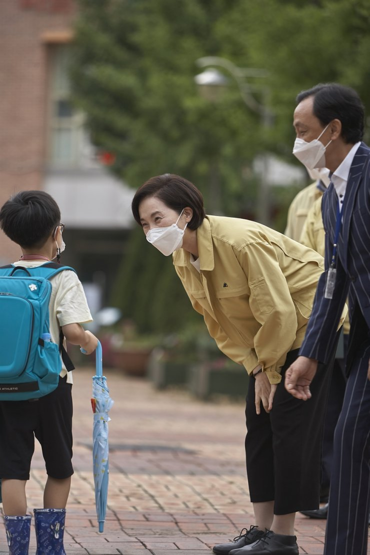 Education Minister Yoo Eun-hae, right, talks with a student at Gocheok Elementary School in Seoul, Monday, during her visit to inspect quarantine measures there. Most elementary schools start their second semesters this week, and schools across the country are providing in-person or online classes according to the social distancing rules applied to their respective regions. Yonhap