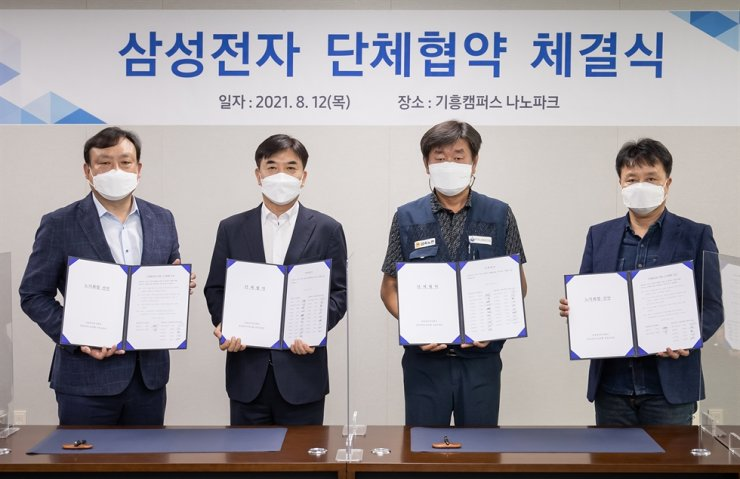 Samsung Electronics' labor unions and management signed their first collective agreement at the company's Kiheung campus in Yongin, Gyeonggi Province, Thursday. From left are Samsung Electronics' Head of Device Solutions HR Choi Wan-woo, President Kim Hyun-suk, Federation of Korean Trade Unions' Head of Metal Craftsmanship Kim Man-jae and Samsung Electronics' Office Workers' Union Head Kim Hang-yeol. Courtesy of Samsung Electronics