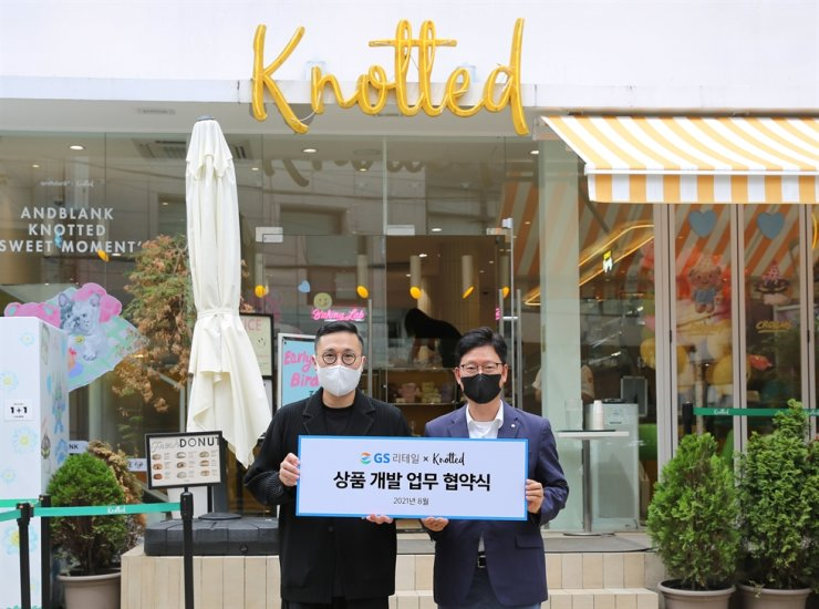 GS Retail's head of merchandising Ahn Byung-hoon, right, poses with Knotted CEO Joon Lee, at a Knotted store in Seoul, Sunday. The two signed an agreement on developing donut products to be sold at GS convenience stores across the country. Courtesy of GS Retail