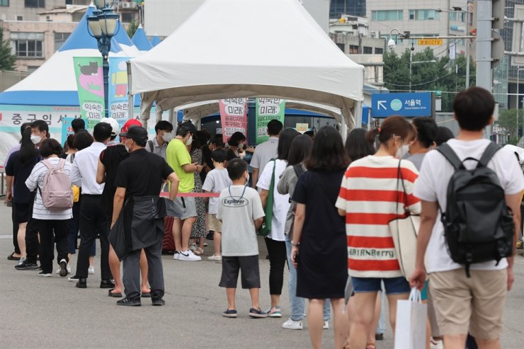 People stand in line for coronavirus tests at a testing center near Seoul Station, Sunday. Yonhap