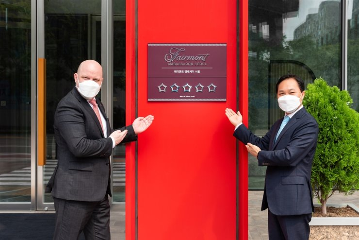 Carl Gagnon, left, general manager of Fairmont Ambassador Seoul, and Kim Gi-seop, CEO of Parc.1 Hotel Management, pose during a plaque unveiling ceremony to mark the hotel's winning of the five-star certification in front of the hotel in Yeouido, Monday. Courtesy of Fairmont Ambassador Seoul