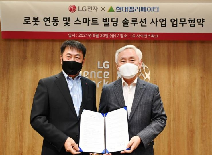 Kwon Soon-hwang, left, head of LG Electronics' Business Solutions division, and Hyundai Elevator CEO Song Seung-bong, pose after signing a memorandum of understanding at LG Science Park in Seoul, Friday. Courtesy of LG Electronics