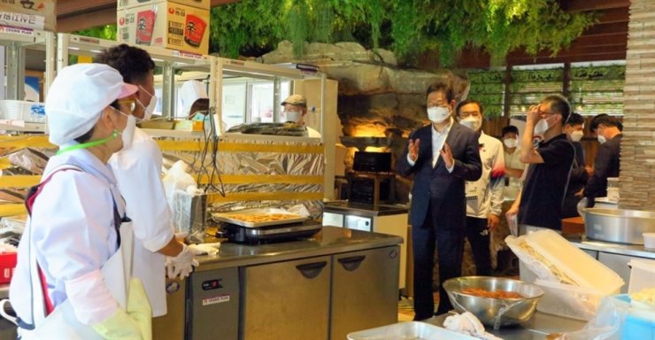 Hwang Hee, center, the minister of culture, sports and tourism, visits Team Korea's meal service center, set up at the Henn na Hotel in Tokyo, on July 24. Yonhap