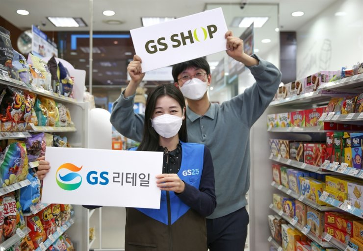 Two workers at GS Retail hold GS Retail and GS Shop signs at a GS25 convenience store in Seoul in this 2020 file photo. Korea Times file