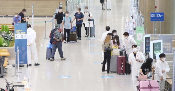 In this Aug. 3 file photo, foreign arrivals follow instructions from health care workers at Incheon International Airport. Yonhap
