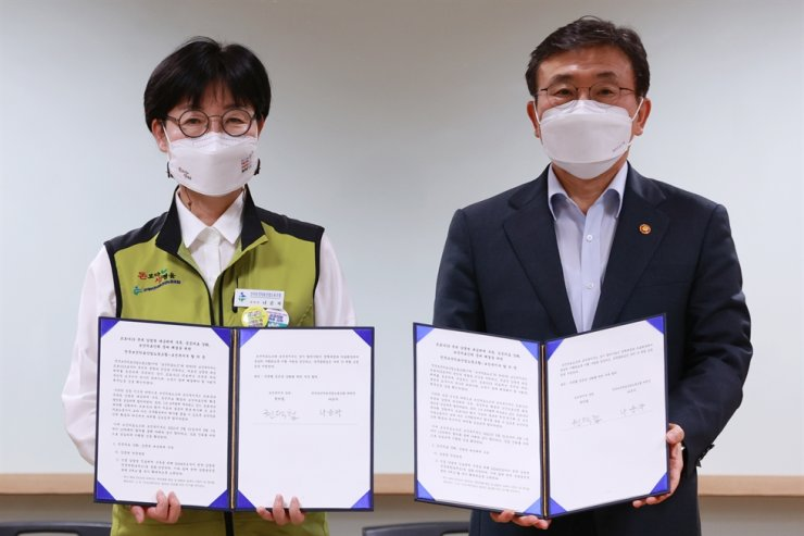 Na Soon-ja, left, the head of the Korean Health and Medical Workers' Union, and Kwon Deok-cheol, the minister of health and welfare, hold their documented agreement after their last-ditch negotiations at the Korea Institute for Healthcare Accreditation in Seoul, Thursday. Yonhap