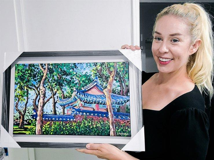 Tahni Osterman poses with a painting. / Courtesy of Otahni Studio