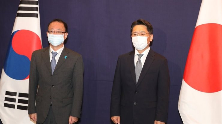 This file photo, taken June 21, shows South Korea's chief nuclear negotiator, Noh Kyu-duk, right, and his Japanese counterpart, Takehiro Funakoshi, posing before their talks in Seoul. Yonhap