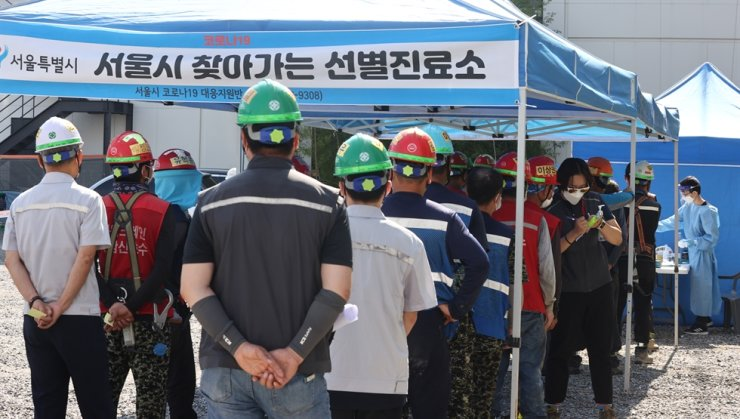 People line up to take a COVID-19 test at a temporary screening center on a construction site in southern Seoul, Friday. The number of daily new coronavirus infections reached a record high of 2,434, Thursday, following the Chuseok holiday period. Yonhap