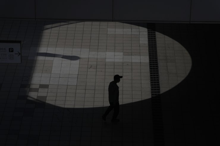 A visitor wearing a face mask to help curb the spread of the coronavirus is silhouetted while walking past outside of a shopping mall in Seoul, Sept. 13. AP-Yonhap