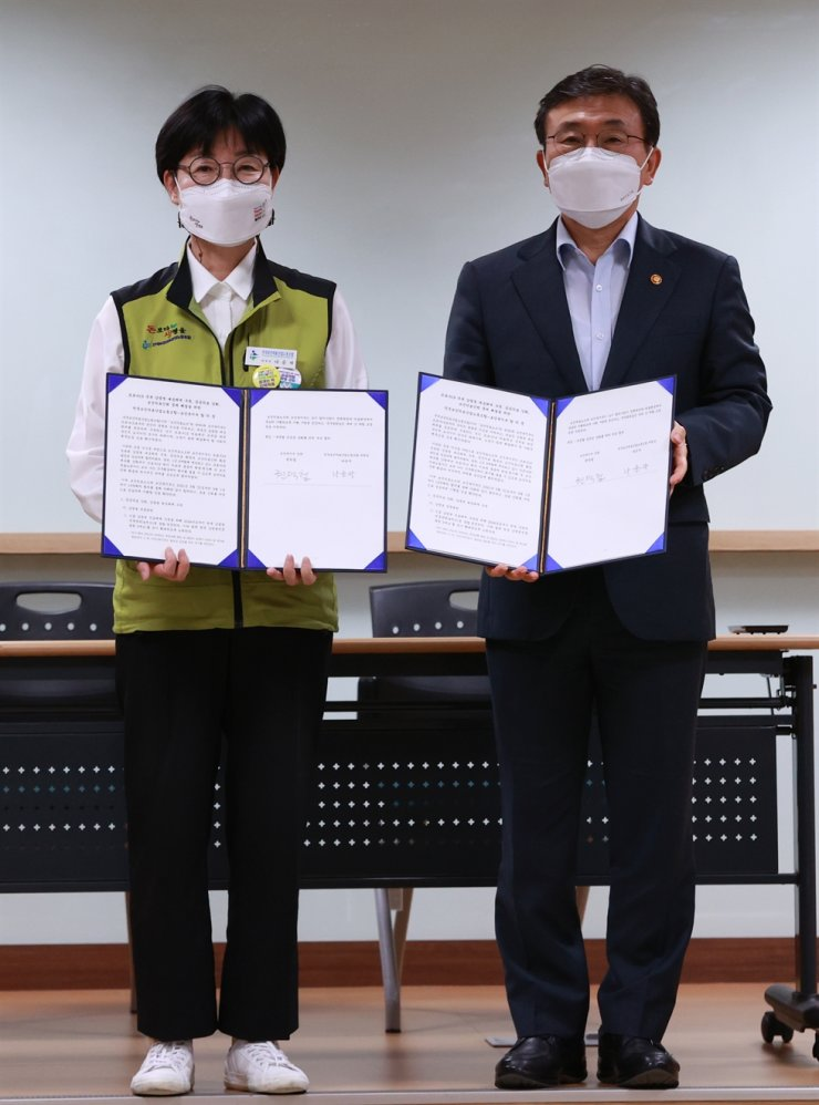Na Soon-ja, left, president of the Korean Health and Medical Workers' Union, and Health Minister Kwon Deok-cheol pose after signing an agreement to improve medical workers' working conditions, at the Korea Institute for Healthcare Accreditation building in Seoul, early Thursday morning. As they reached an agreement, the union called off its strike slated to begin later in the day, and the government will come up with measures by October to support health workers at COVID-19 testing sites and hospitals who have suffered from burnout and fatigue due to a workforce shortage. Yonhap