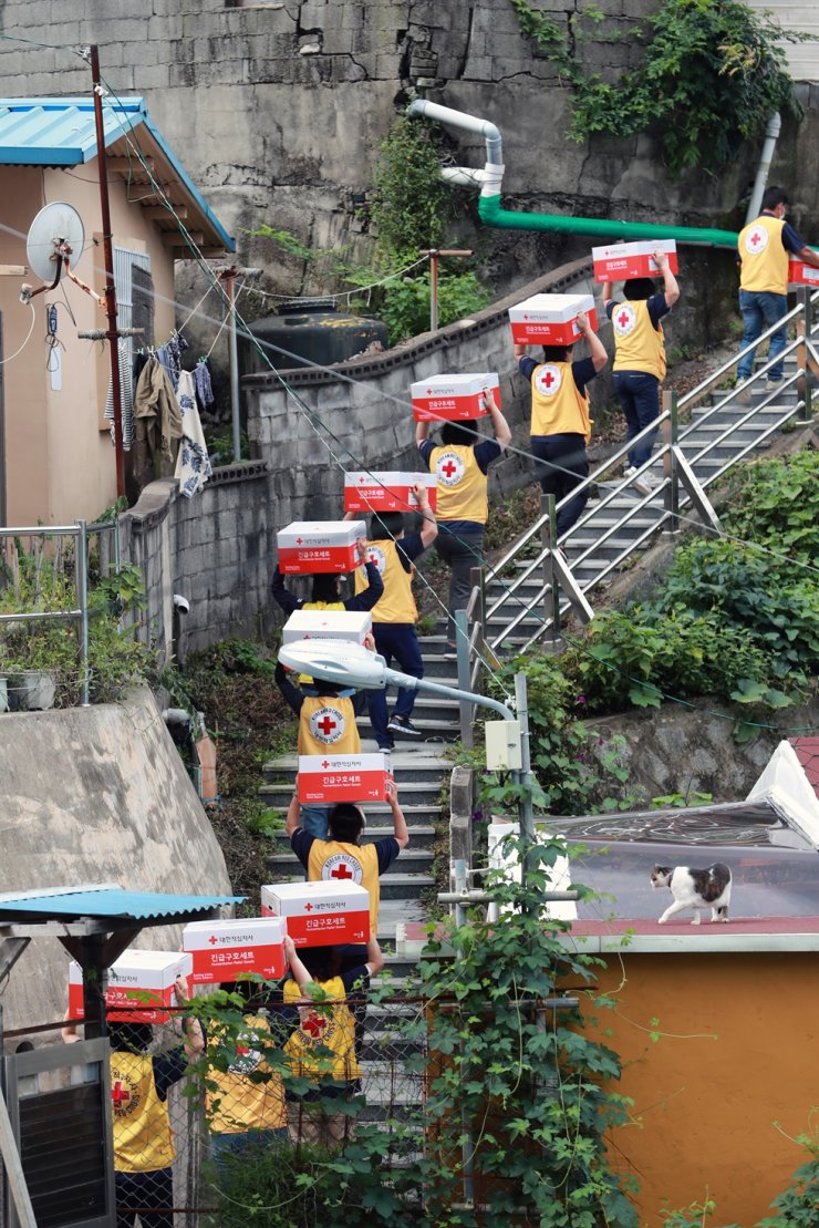 Red Cross workers carrying relief kits packed with daily necessities walk up the stairs in a residential area of Busan, Monday, to deliver them to impoverished people ahead of the upcoming Chuseok long weekend, which runs from Sept. 18 to 22. Yonhap