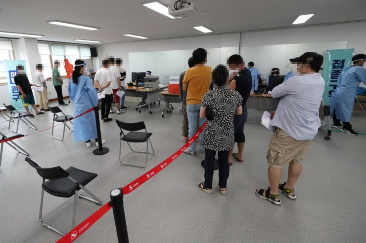 Foreign residents wait to receive COVID-19 vaccine shots at a vaccination center in Gwangju, Sunday. Yonhap