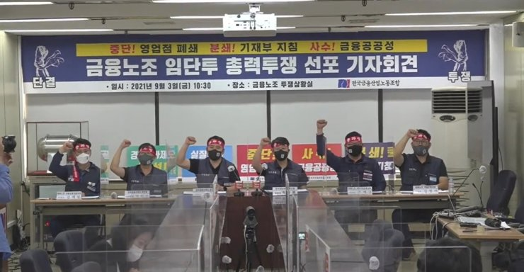 The Korean Financial Industry Union (KFIU) members chant during a press conference at the organization's headquarters in Seoul, Friday. / Screen capture from YouTube