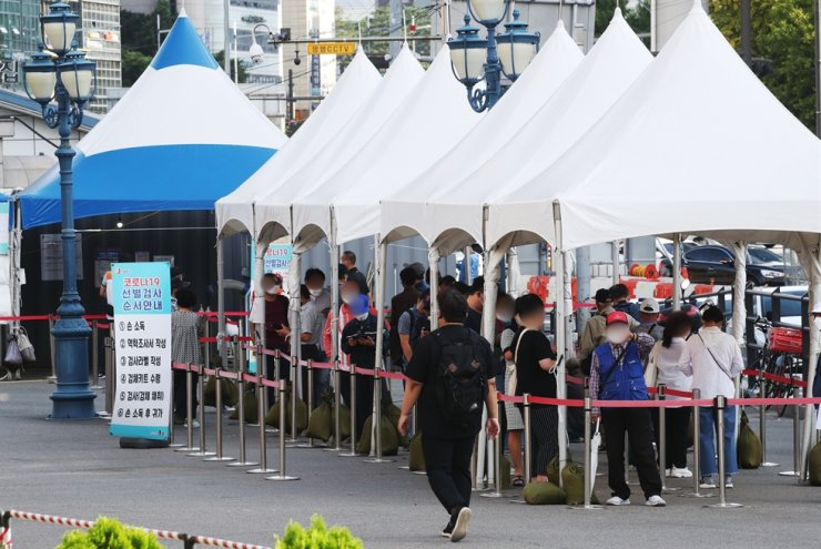 People stand in line to receive a coronavirus test at a testing center near Seoul Station, Monday. Yonhap