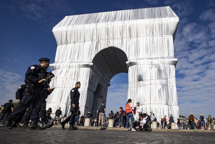 Police patrol as people gather around the fully wrapped Arc de Triomphe monument, part of an art installation titled 'L'Arc de Triomphe, Wrapped' by the late Bulgarian-born US artist Christo, in Paris, France, Sept. 18. EPA-Yonhap