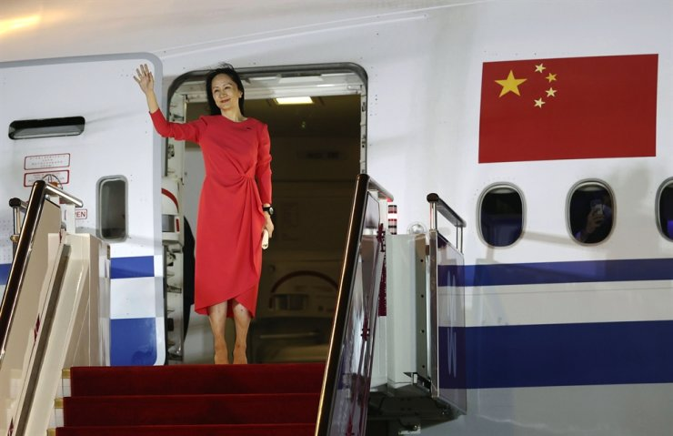 In this photo released by China's Xinhua News Agency, Huawei CFO Meng Wanzhou waves as she steps out of an airplane after arriving at Shenzhen Bao'an International Airport in Shenzhen in southern China's Guangdong Province, Sept. 25. Xinhua via AP-Yonhap
