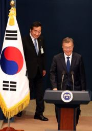 President Moon Jae-in enters the presidential press room in Cheong Wa Dae to announce his nomination of then-South Jeolla Province Governor Lee Nak-yon, at the rear, as his first prime minister, in this May 10, 2017 photo. Korea Times file