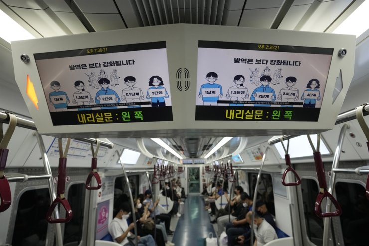 Digital screens showing precautionary measures to take against COVID-19 are seen on a subway train in Seoul, Sept. 3. AP-Yonhap
