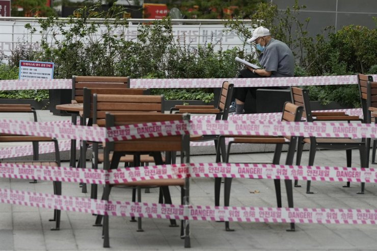 A man wearing a face mask reads a newspaper next to chairs and tables taped for social distancing and a precaution against the coronavirus at a shopping street in Seoul, Aug. 27. AP-Yonhap