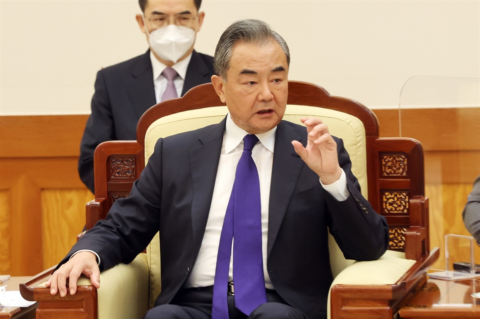 President Moon Jae-in bumps fists with Chinese Foreign Minister Wang Yi during the latter's visit to Cheong Wa Dae, Wednesday. Yonhap