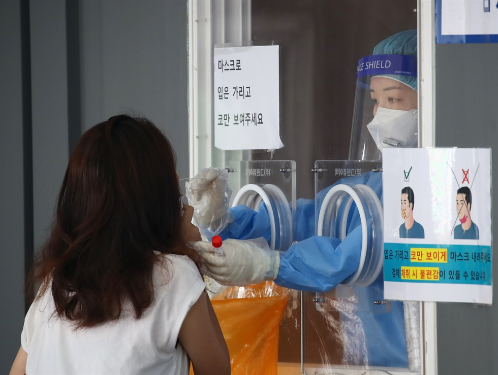 People wait in line to receive a coronavirus test at a testing center in Songpa District of Seoul, Sunday. Yonhap